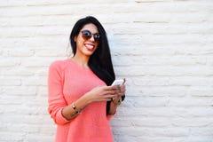 Mujer latina joven que usa su teléfono móvil Foto de archivo