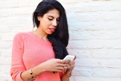 Mujer latina joven que usa su teléfono móvil Fotografía de archivo libre de regalías