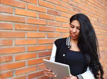 Mujer latina joven que usa una tableta al aire libre fotos de archivo