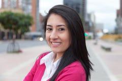 Mujer latina moderna con un chaleco rosado afuera en la ciudad Fotografía de archivo