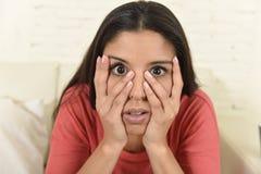 Mujer latina que sienta en casa el sofá del sofá en película de terror asustadiza de observación de la televisión de la sala de e Fotos de archivo libres de regalías