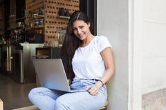 Mujer latina sonriente que le mira mientras que trabaja en el red-libro durante hora de la almuerzo Imagen de archivo libre de regalías