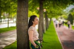 Mujer leanning en árbol Foto de archivo