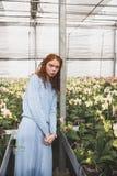 Mujer lening en haz cerca de las flores Foto de archivo