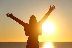 Mujer libre que aumenta los brazos que miran el sol en la salida del sol Foto de archivo libre de regalías