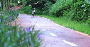 Mujer libre que completa un ciclo en el parque soleado de la mañana