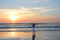 Mujer libre que disfruta de tiempo en la playa en la salida del sol Imagenes de archivo