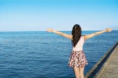 Mujer libre que disfruta del verano con los brazos abiertos en la playa Imágenes de archivo libres de regalías