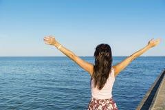 Mujer libre que disfruta del verano con los brazos abiertos en la playa Fotografía de archivo