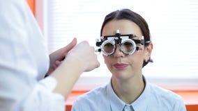 Mujer linda con el marco de ensayo para la determinación de la lente almacen de metraje de vídeo