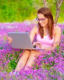 Mujer linda con el ordenador portátil al aire libre Fotos de archivo