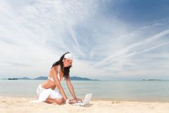 Mujer linda con el ordenador portátil en la playa del verano Fotografía de archivo