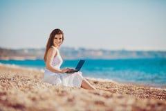 Mujer linda con el ordenador portátil blanco en la playa del verano fotos de archivo