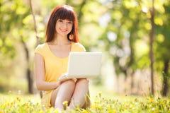 Mujer linda con el ordenador portátil en el parque con los dientes de león Foto de archivo libre de regalías