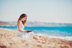 Mujer linda con el ordenador portátil blanco en la playa del verano Foto de archivo