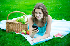 Mujer linda con la cesta de la comida campestre y frutas usando el teléfono elegante en el PA Fotos de archivo