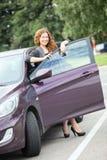 Mujer linda con las llaves que se colocan cerca de propio nuevo coche Imagen de archivo