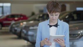 Mujer linda confiada del retrato en desgaste formal usando sus soportes de la tableta delante de los coches borrosos en salón del almacen de video