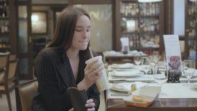 Mujer linda del retrato en el traje que se sienta en el restaurante que come los alimentos de preparación rápida Cola de consumic metrajes