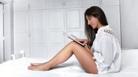 Mujer linda descalza del tiro lleno que se sienta en el libro de lectura blanco acogedor de la cama en el dormitorio moderno almacen de video