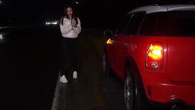 Mujer linda en la chaqueta blanca, intentando parar los coches en una carretera para conseguir una cierta ayuda almacen de video