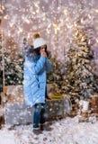 Mujer linda en manos que se calientan y la situación abajo de la chaqueta azul cerca de s Fotografía de archivo