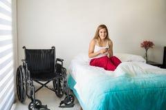 Mujer linda en silla de ruedas usando smartphone Foto de archivo libre de regalías