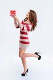 Mujer linda feliz en el vestido que sostiene la caja de regalo Imagen de archivo