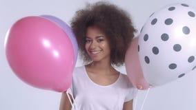 Mujer linda feliz joven con los globos que sonríe, ascendente cercano almacen de video