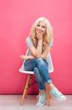 Mujer linda feliz que se sienta en la silla Imagen de archivo libre de regalías
