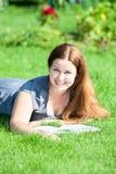 Mujer linda joven con un libro abierto que descansa sobre verde Imagen de archivo