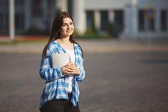 Mujer linda joven del estudiante con los libros en las manos que se colocan por mañana Fotos de archivo libres de regalías