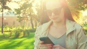 Mujer linda joven del estudiante del pelirrojo en chaqueta con el teléfono celular en sus manos que presentan al aire libre en la almacen de metraje de vídeo