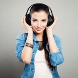 Mujer linda joven en equipo azul del dril de algodón que disfruta de la música Imágenes de archivo libres de regalías