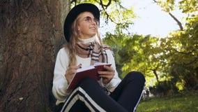 Mujer linda joven que hace algunas notas en su lechería mientras que se sienta en la hierba en el fondo del parque almacen de metraje de vídeo