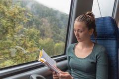Mujer linda joven que lee un libro mientras que viaja en tren foto de archivo