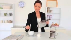 Mujer linda joven que lee un periódico mientras que bebe un café almacen de metraje de vídeo