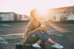 Mujer linda milenaria del inconformista en tejado en la puesta del sol imagen de archivo libre de regalías