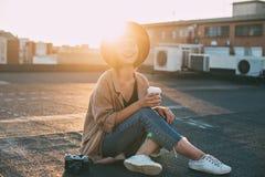 Mujer linda milenaria del inconformista en tejado en la puesta del sol imágenes de archivo libres de regalías