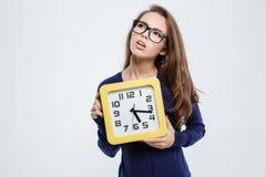 Mujer linda pensativa que sostiene el reloj de pared Imágenes de archivo libres de regalías