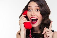 Mujer linda preciosa emocionada en estilo retro que habla en el teléfono Foto de archivo