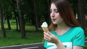 Mujer linda que come el helado en el parque almacen de metraje de vídeo