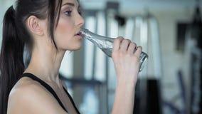 Mujer linda que ejercita en el gimnasio almacen de metraje de vídeo