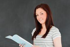 Mujer linda que lee sus notas Imagenes de archivo