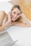 Mujer linda que llama por teléfono con su smartphone que miente en su cama Fotos de archivo libres de regalías
