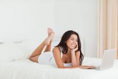 Mujer linda que miente en cama con las piernas cruzadas Fotografía de archivo