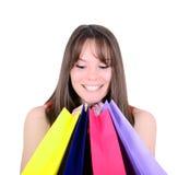 Mujer linda que mira en los panieres coloridos aislados en blanco Imagen de archivo libre de regalías