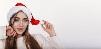 Mujer linda que mira la cámara y toching su sombrero de la Navidad Fotos de archivo libres de regalías