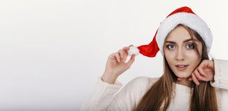 Mujer linda que mira la cámara y toching su sombrero de la Navidad Imagen de archivo libre de regalías