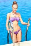 Mujer linda que se coloca en escalera de la piscina Imagenes de archivo